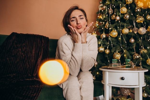 Szczęśliwa kobieta siedzi na kanapie przez choinkę