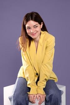 Szczęśliwa kobieta siedzi na krześle średnim strzału