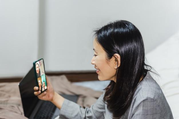 Szczęśliwa kobieta siedzi na łóżku, co wideo rozmowy na smartfonie.