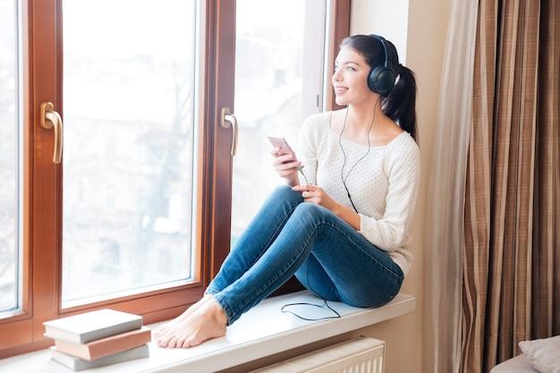 Szczęśliwa kobieta siedzi na parapecie i słucha muzyki w słuchawkach w domu
