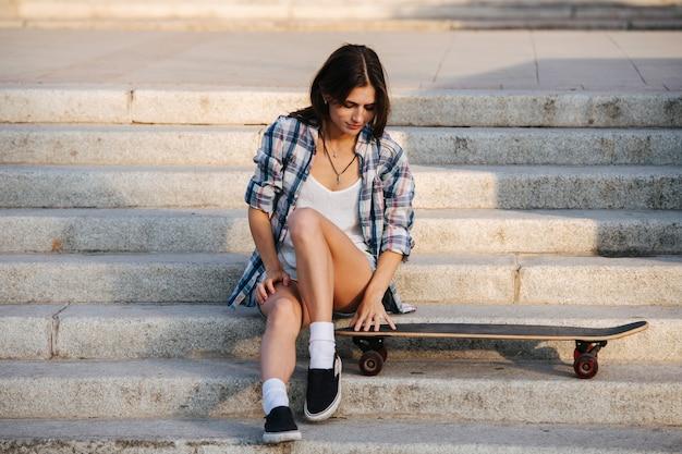 Szczęśliwa kobieta siedzi na schodach i patrzy ostrożnie na swoją deskorolkę