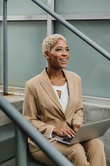 Szczęśliwa kobieta siedzi na schodach ze swoim laptopem