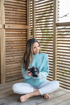 Szczęśliwa kobieta siedzi na tarasie z aparatu fotograficznego