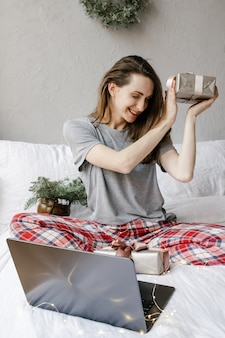 Szczęśliwa kobieta siedzi przed ekranem komputera z pudełkiem w dłoniach w domu i pokazuje swój prezent za pośrednictwem połączenia wideo