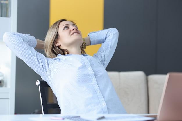 Szczęśliwa kobieta siedzi przy stole roboczym i patrzy w sufit