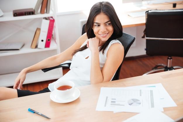 Szczęśliwa kobieta siedzi przy stole z kawą i odwraca wzrok w biurze