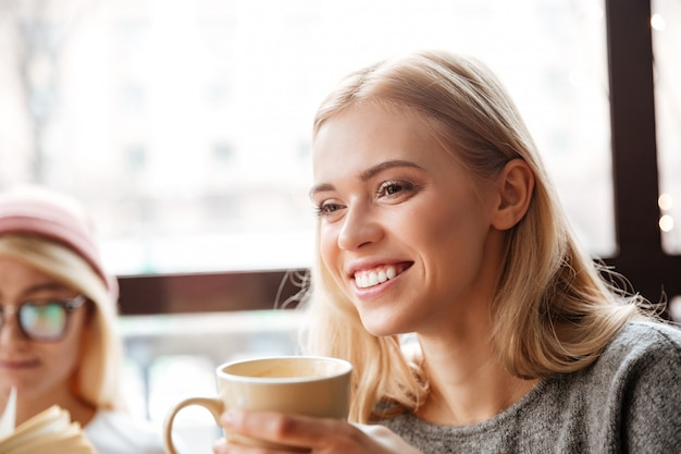 Szczęśliwa kobieta siedzi w kawiarni i picia kawy.