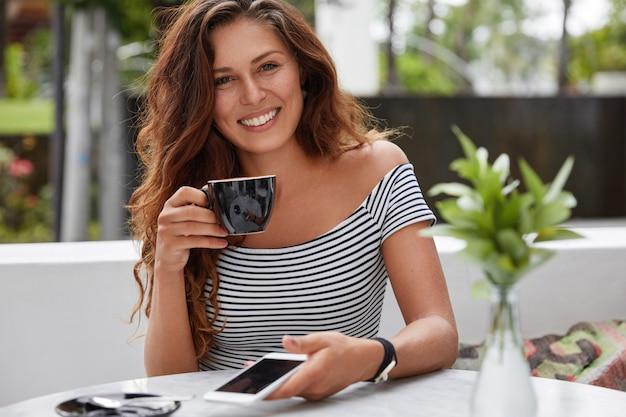 Szczęśliwa kobieta siedzi w kawiarni