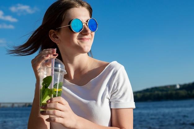 Szczęśliwa kobieta siedzi w niebieskich okularach na tle morza, a niebo trzyma mojito i uśmiecha się, odpoczywa na plaży i patrzy w dal
