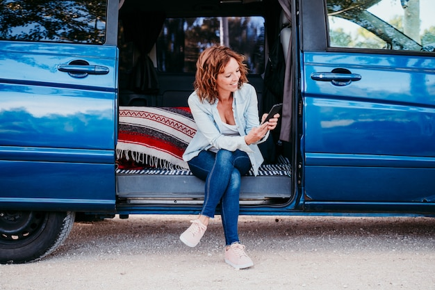 Szczęśliwa kobieta siedzi w niebieskim van i zabawy. koncepcja podróży. kobieta używa telefon komórkowego