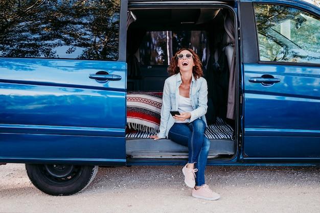 Szczęśliwa kobieta siedzi w niebieskim van i zabawy. koncepcja podróży