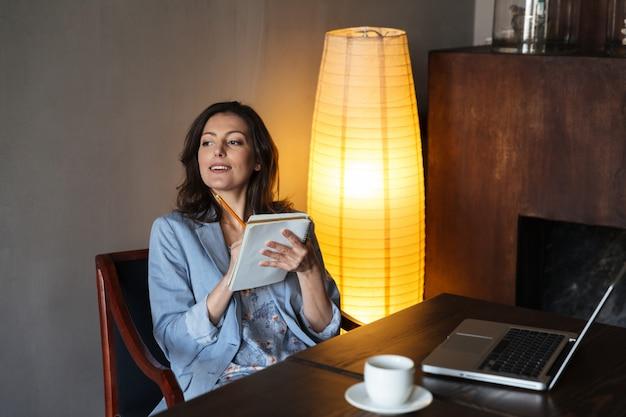 Szczęśliwa kobieta siedzi w pomieszczeniu pisać notatki.