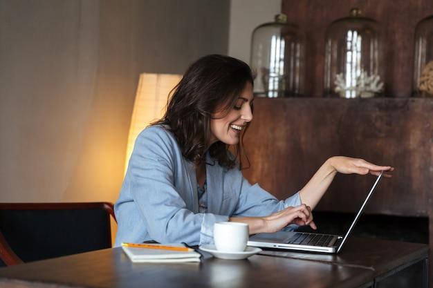 Szczęśliwa kobieta siedzi w pomieszczeniu przy użyciu komputera przenośnego