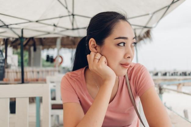 Szczęśliwa kobieta siedzi w restauracji na plaży.