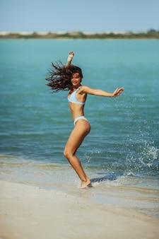 Szczęśliwa kobieta skacząca z radości w niebieskim bikini na plaży opalona szczupła dziewczyna w stroju kąpielowym ciesząca się