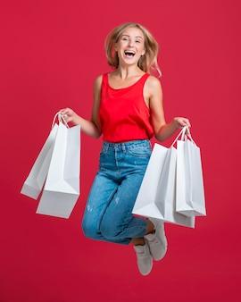 Szczęśliwa kobieta skacze z dużą ilością toreb na zakupy