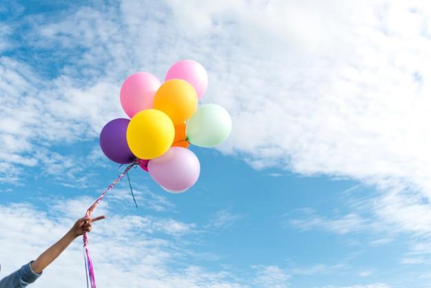 Szczęśliwa kobieta skacze z lotniczymi balonami na łące.