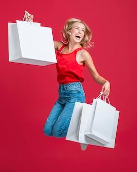 Szczęśliwa kobieta skacze z wieloma torbami na zakupy