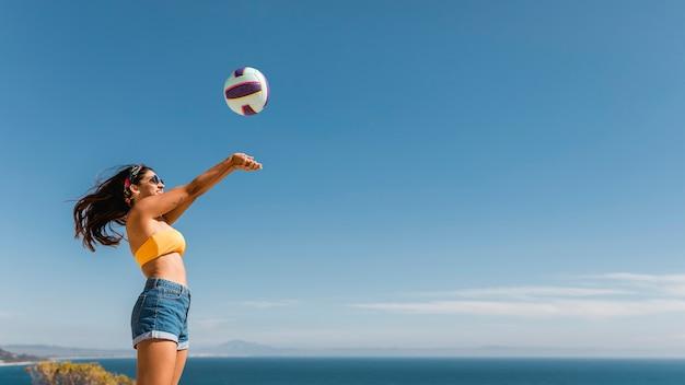 Szczęśliwa kobieta skoki i rzucanie piłki