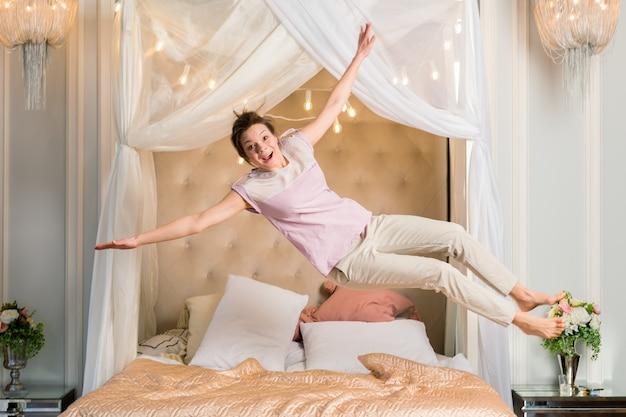 Szczęśliwa kobieta skoki w łóżku