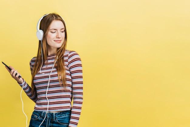 Szczęśliwa kobieta słucha muzyka z kopii przestrzenią