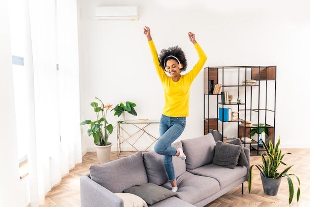 Szczęśliwa kobieta słucha muzyki skacząc i tańcząc na kanapie w domu