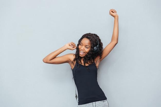 Szczęśliwa kobieta słucha muzyki w słuchawkach na szarej ścianie