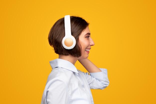 Szczęśliwa kobieta słuchająca muzyki przez słuchawki