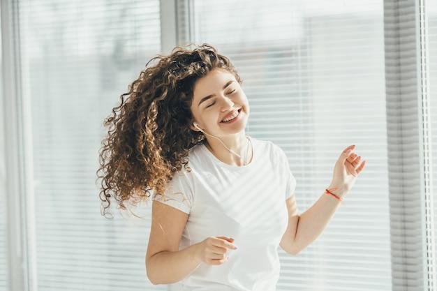 Szczęśliwa kobieta słuchająca muzyki przy oknie