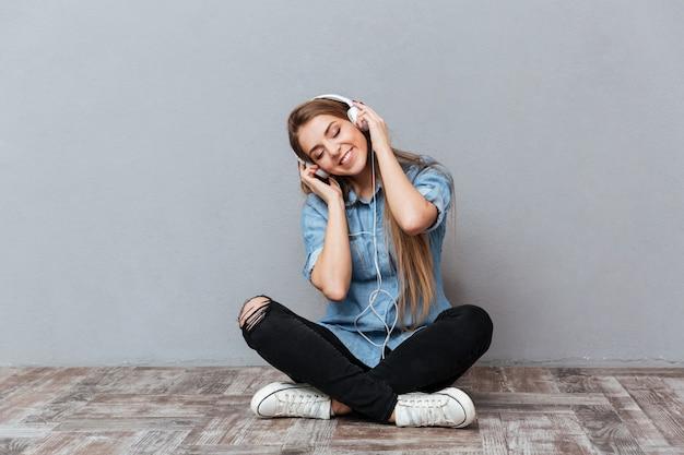 Szczęśliwa kobieta słuchania muzyki na podłodze