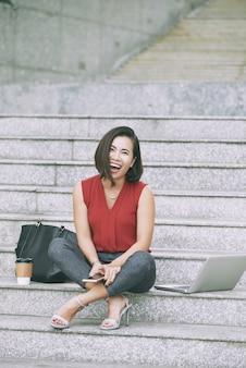 Szczęśliwa kobieta śmiechu siedząca na marmurowych schodach w pobliżu laptopa, torby i kawy na wynos