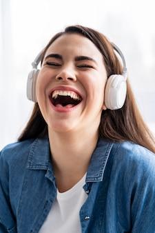Szczęśliwa kobieta, śmiejąc się i słuchając muzyki na słuchawkach