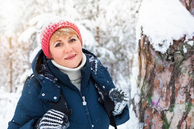 Szczęśliwa kobieta spaceru w zimowym lesie. w parku marznie kobieta w średnim wieku.