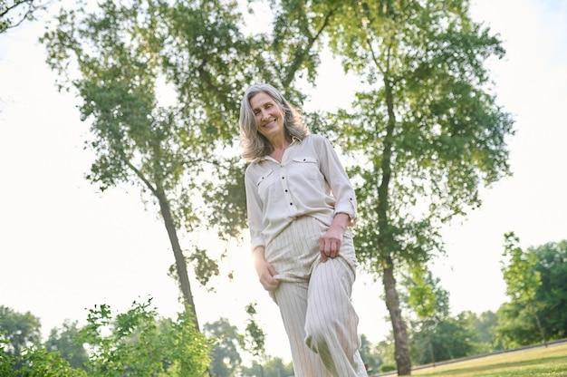 Szczęśliwa kobieta spędzająca wolny czas w zielonym parku