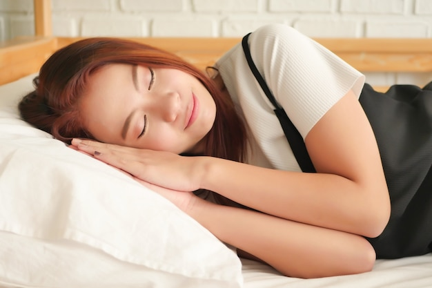 Szczęśliwa kobieta śpi, odpoczywa, ucina sobie drzemkę