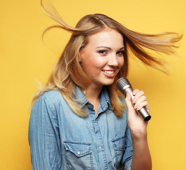 Szczęśliwa kobieta śpiewa w mikrofonie