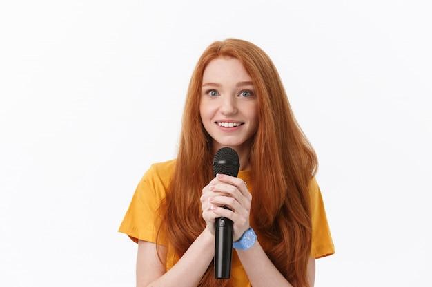 Szczęśliwa kobieta śpiewa z kręconymi włosami trzymając mikrofon izolowanych ponad białym