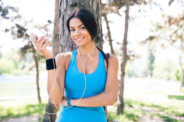Szczęśliwa kobieta sportowy trzymając smartfon na zewnątrz