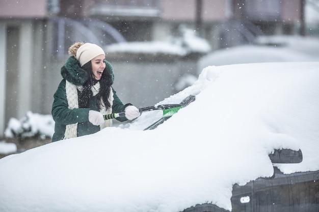 Szczęśliwa kobieta sprzątanie samochodu od śniegu za pomocą pędzla śniegu.