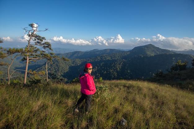 Szczęśliwa kobieta stanąć na szczycie góry patrząc widok z mgły i chmury.