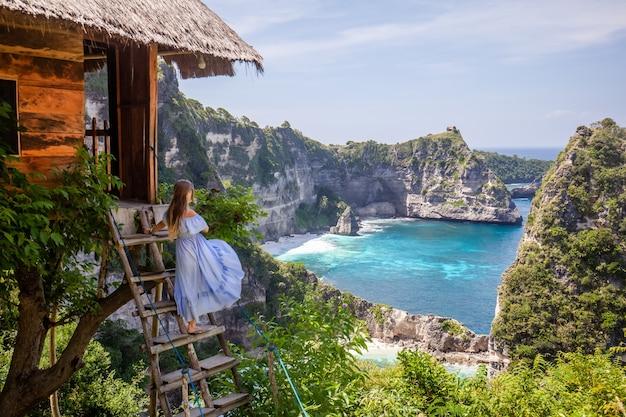 Szczęśliwa kobieta stoi blisko drzewnego domu przy punktem widzenia tysiąc wysp nusa penida