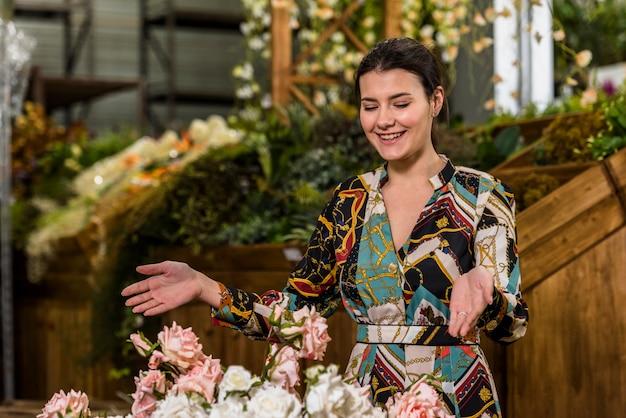 Szczęśliwa kobieta stoi blisko róż w zielonym domu