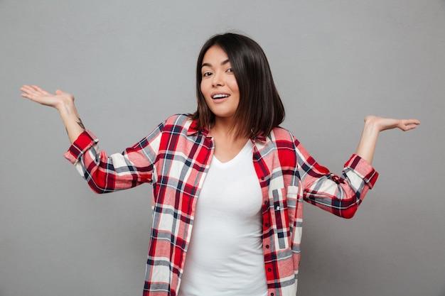Szczęśliwa kobieta stoi nad szarości ściany mienia copyspace
