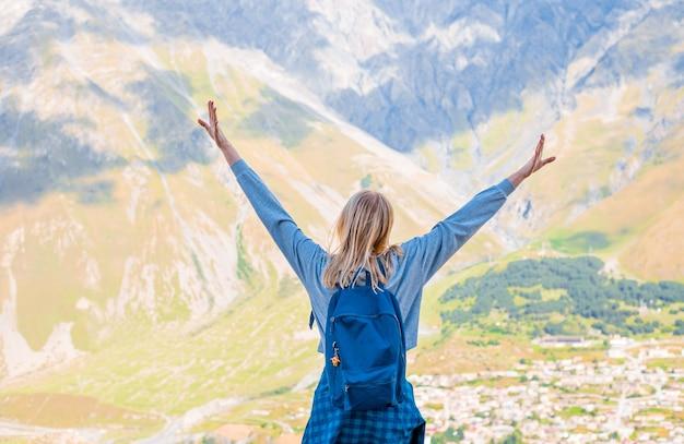 Szczęśliwa kobieta stoi z podniesionymi rękami na tle szczytów górskich.