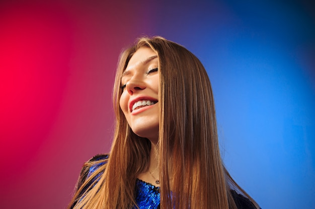 Szczęśliwa kobieta stojąc i uśmiechając się przed kolorową ścianą