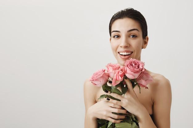 Szczęśliwa kobieta stojąca nago z bukietem róż, uśmiechnięta pochlebnie