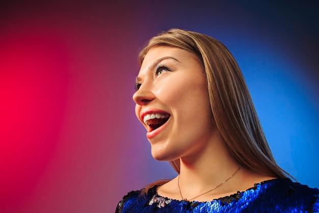 Szczęśliwa kobieta stojąca, uśmiechnięta na kolorowym tle studia. piękny portret kobiety w połowie długości. młoda kobieta zadowala.