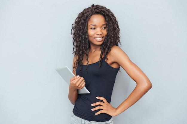Szczęśliwa kobieta stojąca z komputerem typu tablet nad szarą ścianą i odwracająca wzrok