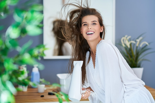 Szczęśliwa kobieta susząca włosy w łazience