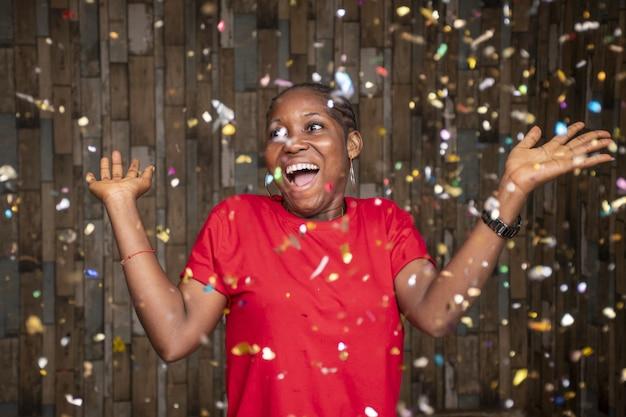 Szczęśliwa kobieta świętująca konfetti przed drewnianą ścianą